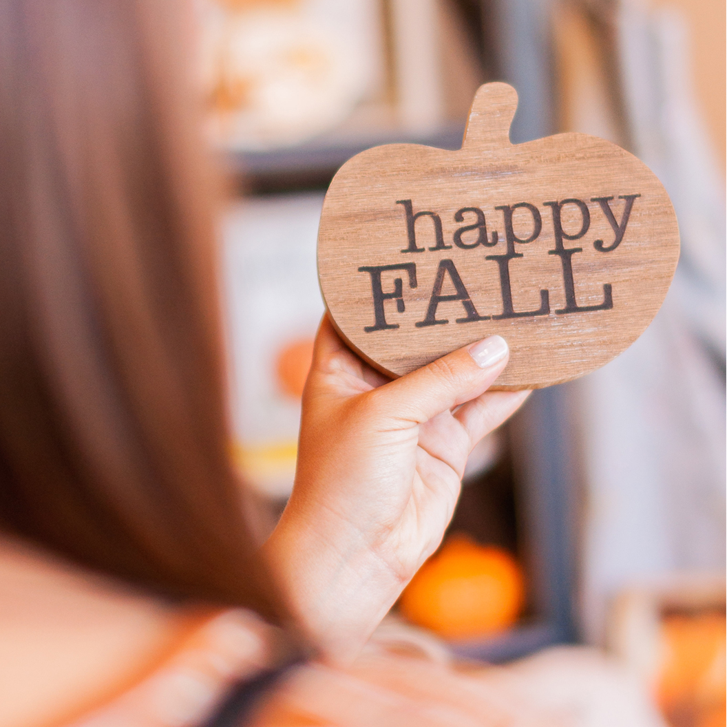 A Flair for Gifts & Home - over the shoulder shot of a girl holding a wooden pumpkin carve out that is engraved with happy FALL