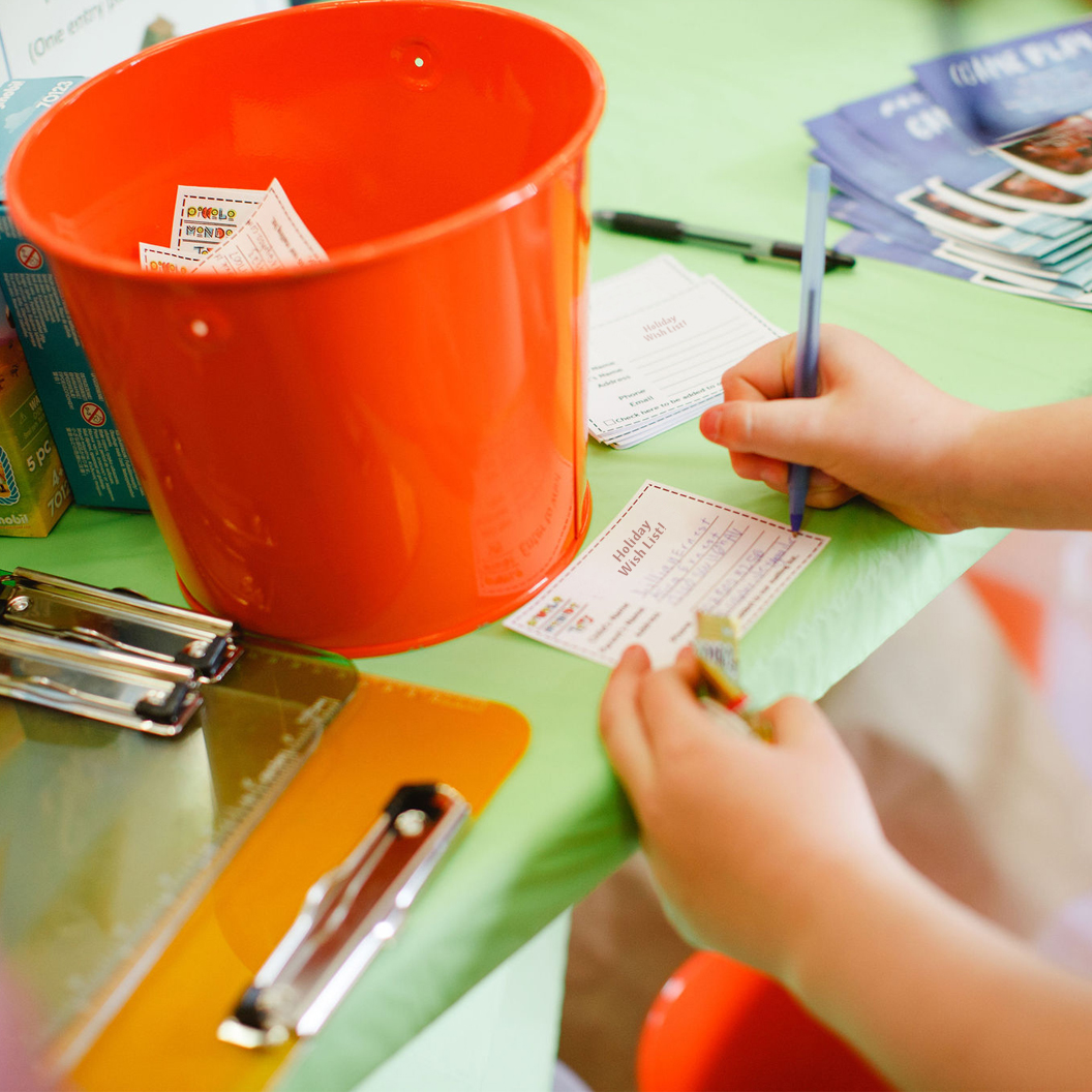Piccolo Mondo Toys - Kid filling out a Holiday Wish List paper on a green table and orange bucket